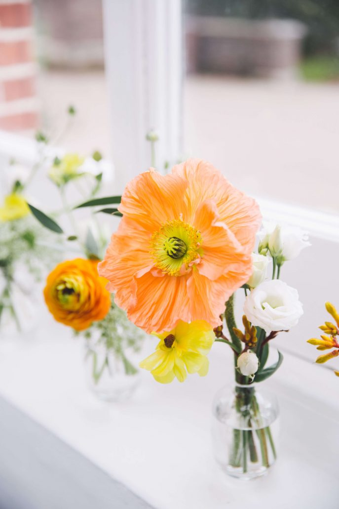 bud vases with orange poppies and ranunculus for a ceremony at Twickenham Town Hall in London