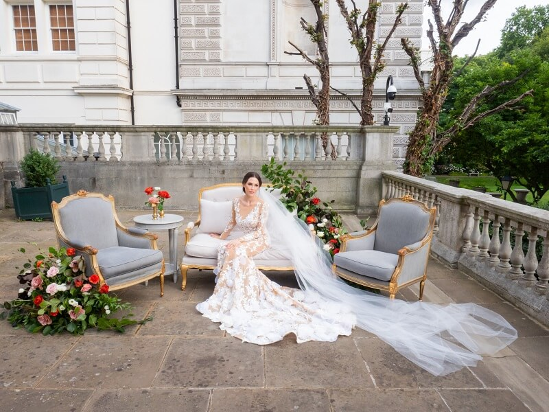 bride sitting on a sofa decorated with flower arrangements at Spencer House